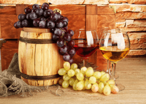 composition of wine,box and grapes on wooden barrel on table on brick wall background