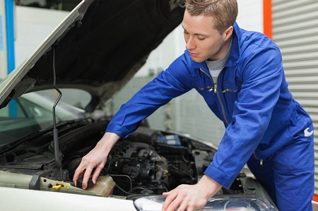 Portrait of male mechanic closing the lid of windshield washer tank