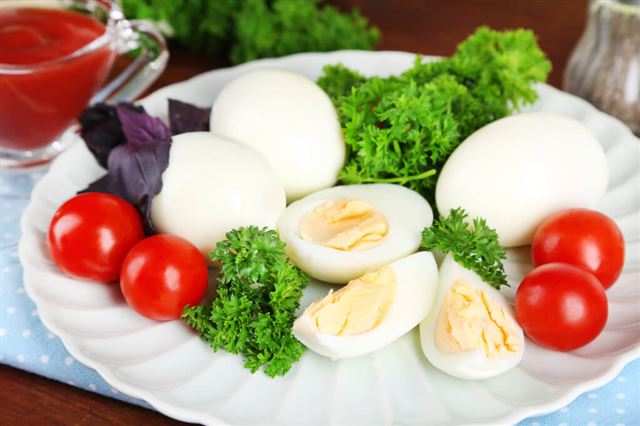 Boiled eggs on plate on napkin on wooden table