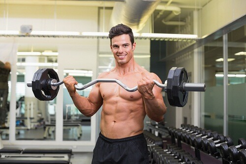 Portrait of a smiling shirtless muscular man lifting barbell in gym