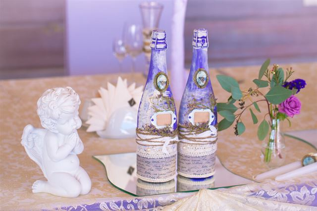 Decoration for wedding table in purple color . Bottle of champag