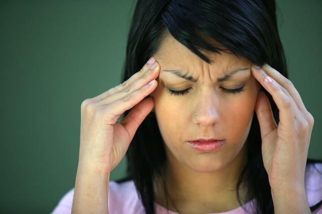 Brunette suffering from tension headache