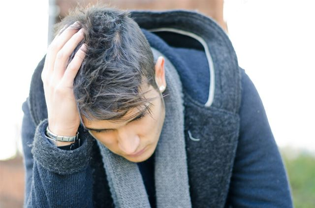 Desperate, sad or upset young man holding his head