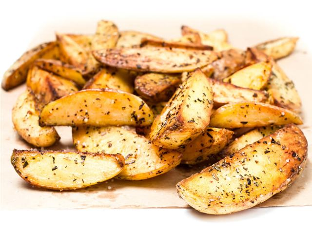 Fried potato wedges country styled with herbs and spices on perchament paper.  Fast food.