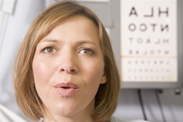 Woman in optometrist's exam room taking deep breath