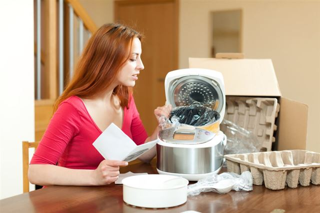Young housewife unpacking and reading user manual for new crock-
