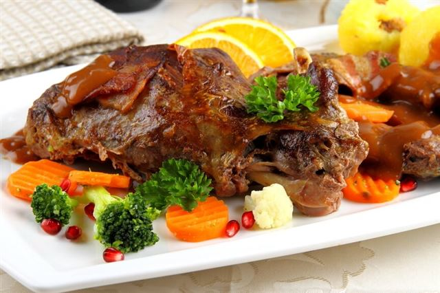 Baked wild rabbit meat with potato dumplings and vegetables