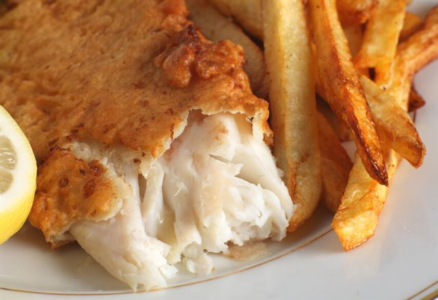 Homemade fish and chips served with a piece of lemon