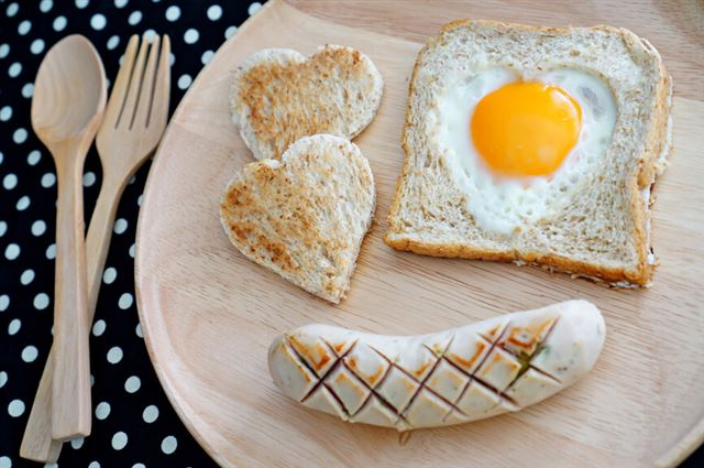 Breakfast consist of toast with fried egg in shape of heart and