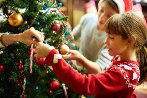 Ребенок с мамой наряжает елку